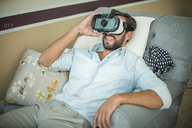 Young man on armchair looking through virtual reality headset