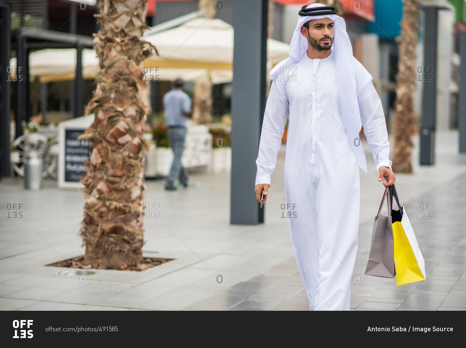 Man wearing traditional middle eastern clothing walking along man wearing traditional middle eastern clothing walking along street carrying shopping bags dubai united sciox Images