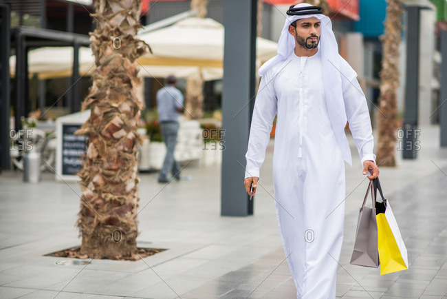 Man wearing traditional middle eastern clothing walking along street carrying shopping bags, Dubai, United Arab Emirates
