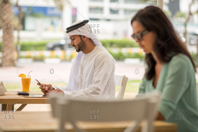 Middle eastern man wearing traditional clothing reading smartphone text at cafe, Dubai, United Arab Emirates