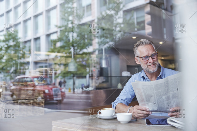 Mature man sitting in cafe, reading newspaper, street reflected in window