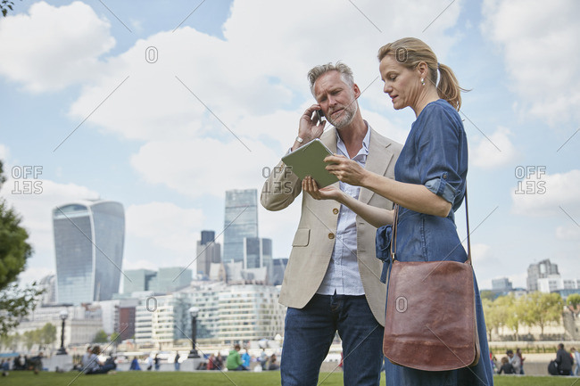 Mature man and woman outdoors, looking at digital tablet, man using smartphone