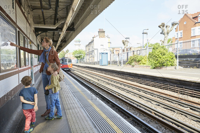 Mother and sons on railway platform looking at wall mounted map