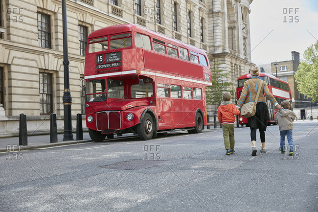 Rear view of mother and sons looking at red double decker bus