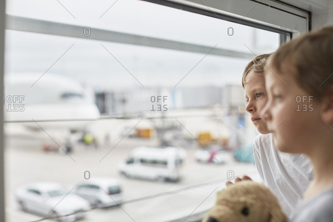 Boys looking out of airport window at runway