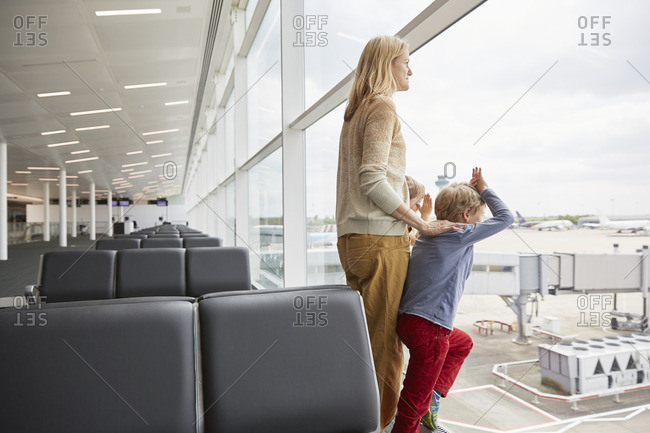Mother and sons in departure lounge looking out of window
