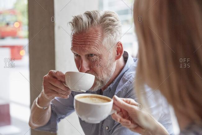 Mature man in coffee shop drinking coffee