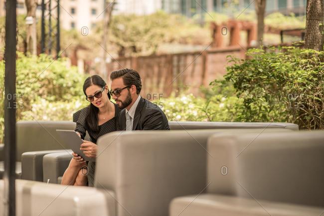 Businessman and woman using digital tablet on hotel garden sofa, Dubai, United Arab Emirates