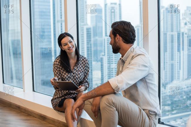 Businesswoman and man sitting at window with skyscraper view, Dubai, United Arab Emirates