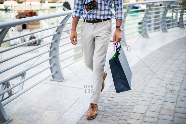 Waist down view of young man strolling on waterfront carrying shopping bag, Dubai, United Arab Emirates