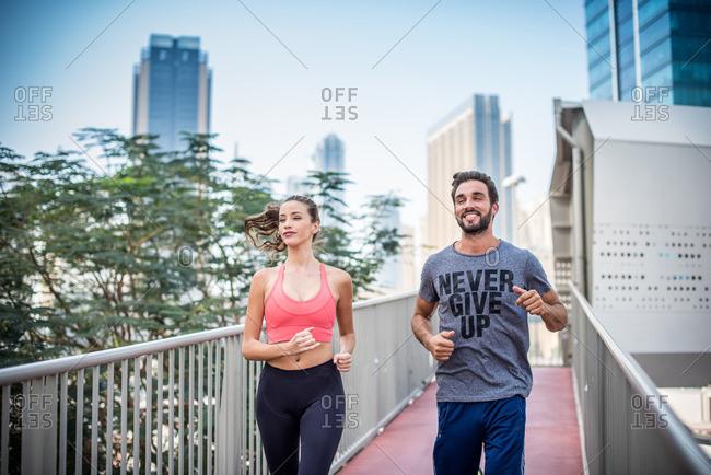 Running couple running on footbridge, Dubai, United Arab Emirates
