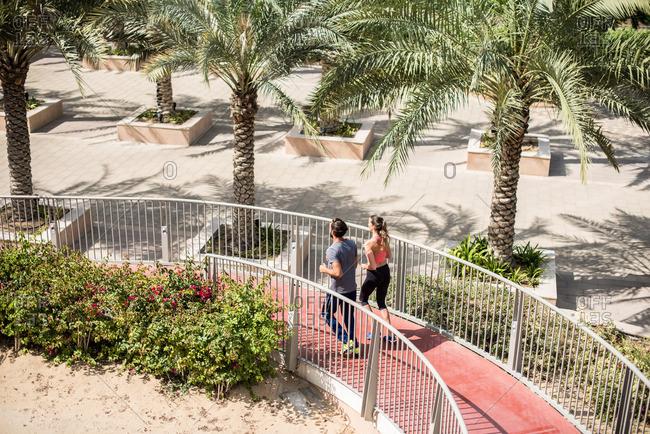 High angle view of running couple running down footbridge, Dubai, United Arab Emirates