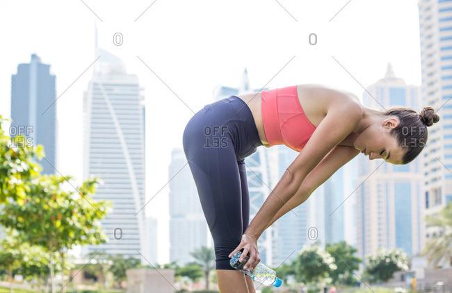 Woman training, taking a break in park, Dubai, United Arab Emirates