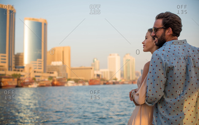 Romantic couple looking out at Dubai marina, United Arab Emirates