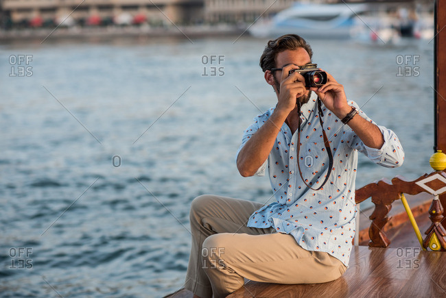 Young man photographing from boat at Dubai marina, United Arab Emirates