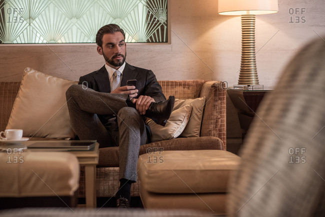 Young businessman sitting on hotel lobby sofa using smartphone