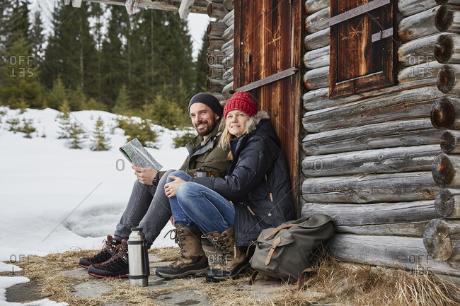 Portrait of couple reading map sitting outside log cabin in winter, Elmau, Bavaria, Germany