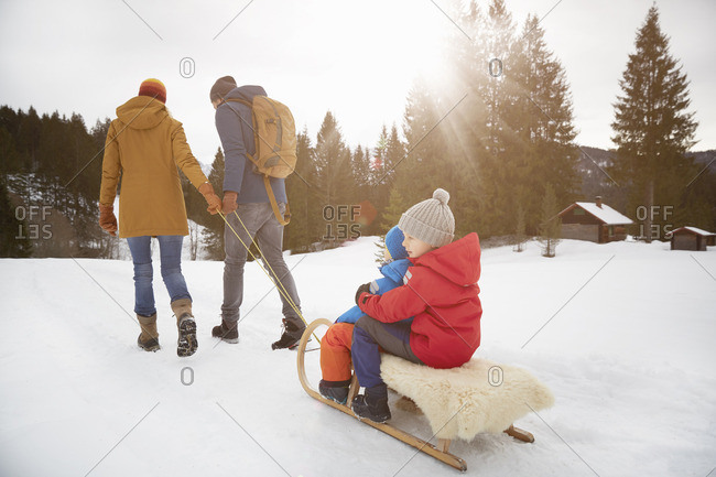 Rear view of parents pulling sons on toboggan in snow landscape, Elmau, Bavaria, Germany