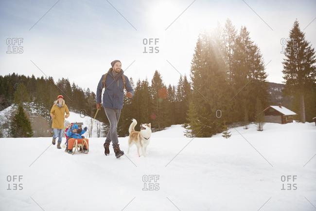 Parents pulling sons on toboggan in snow covered landscape, Elmau, Bavaria, Germany
