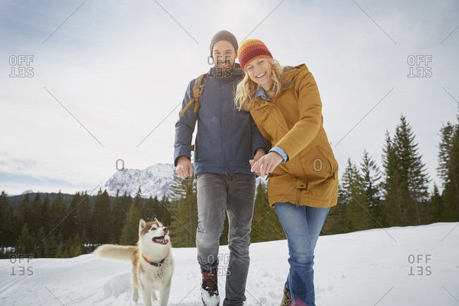 Portrait of couple walking husky in snow covered landscape, Elmau, Bavaria, Germany