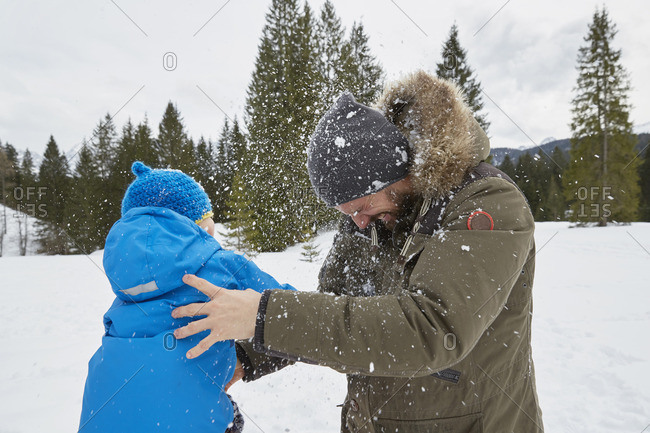 Young man and son having snowball fight in winter, Elmau, Bavaria, Germany