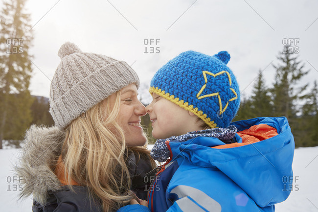 Portrait of mother and son nose to nose in winter, Elmau, Bavaria, Germany