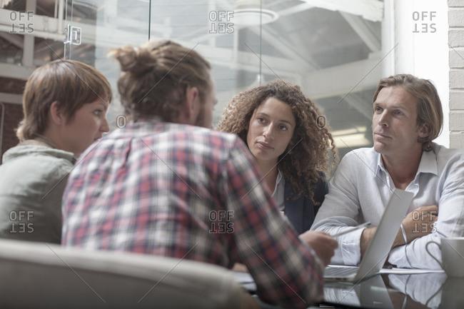 Men and women having team meeting in creative studio