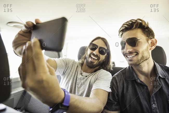 Friends in backseat of car wearing sunglasses taking selfie