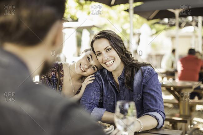 Friends at sidewalk cafe hugging