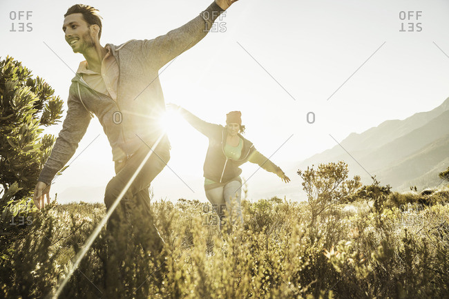 Couple running in field, arms open