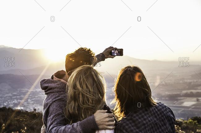 Rear view of friends on hillside taking selfie