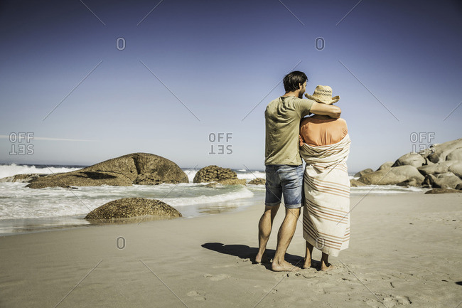 Rear view of couple wrapped in blanket looking out from beach, Cape Town, South Africa