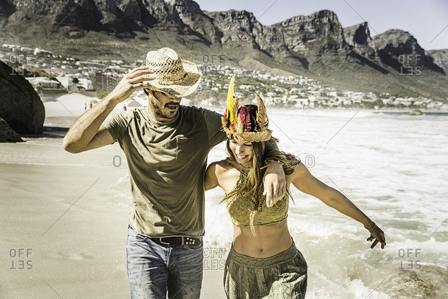 Mid adult couple wearing straw hat and feather headdress running on beach, Cape Town, South Africa