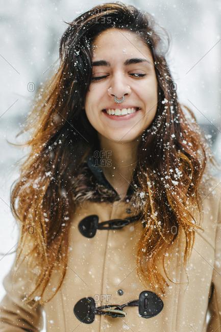 Woman wearing duffle coat in snow, eyes closed smiling