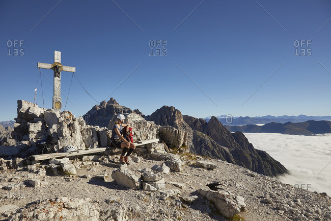 Female hiker sitting on Paternkofel mountain bench, Dolomites, Sexten, South Tyrol, Italy