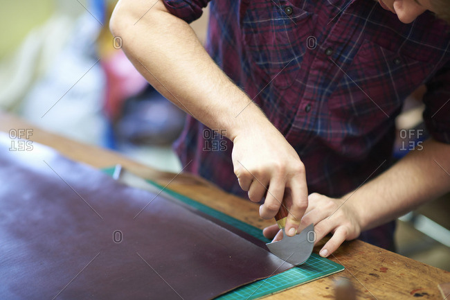 Male worker in leather workshop, using cutting tool to cut leather, mid esction