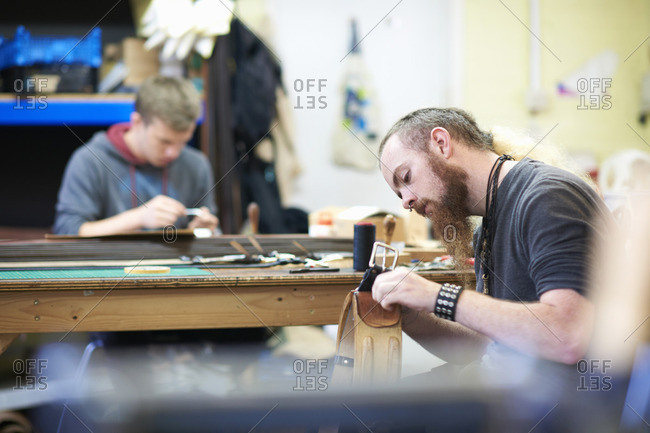 Male worker in leather workshop, sewing up seams around a belt buckle