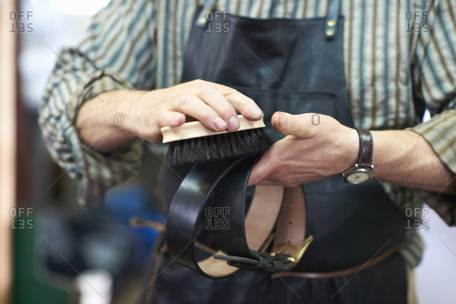 Male worker in leather workshop, polishing belt, mid section