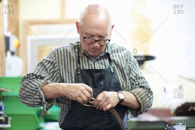 Male worker in leather workshop, polishing belt buckle