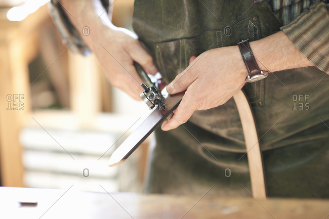 Male worker in leather workshop, punching holes in leather belt, mid section, close-up