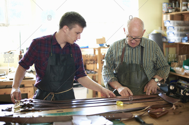 Two male workers in leather workshop, checking leather belts