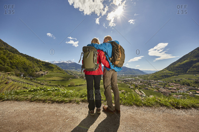 Mature couple standing by roadside, looking at view, rear view, Meran, South Tyrol, Italy