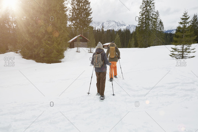 Couple snowshoeing across snowy landscape, rear view, Elmau, Bavaria, Germany