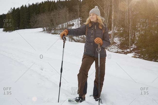 Mature woman on snow shoes, holding ski poles, Elmau, Bavaria, Germany