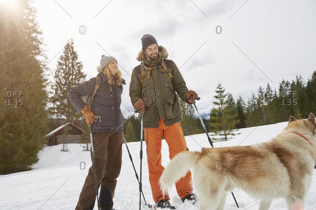 Couple snowshoeing across snowy landscape, Elmau, Bavaria, Germany