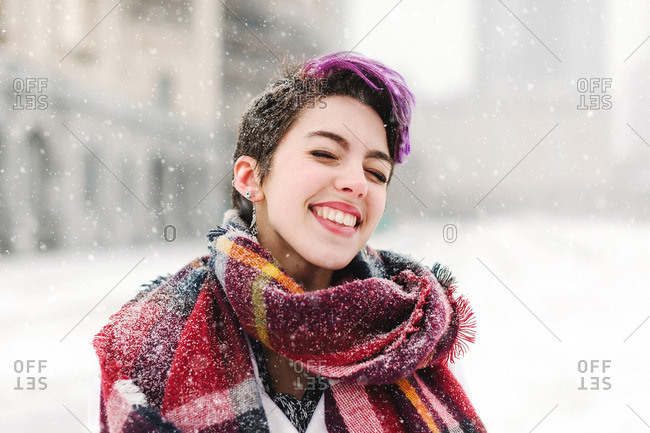 Portrait of young woman standing in front of the Christian Science Centre and Prudential building with snow, Boston, Massachusetts, USA