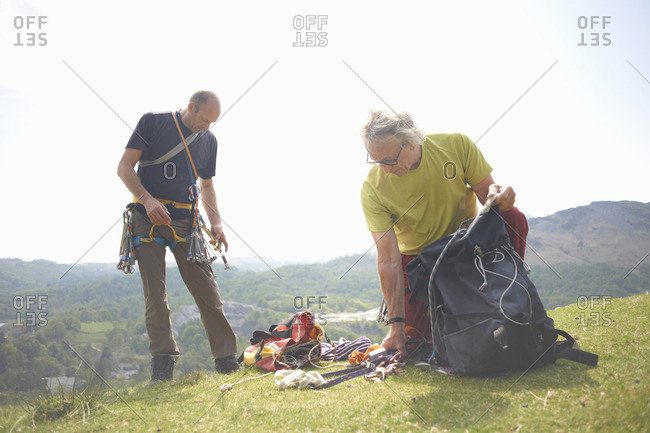 Rock climbers on hilltop preparing climbing equipment