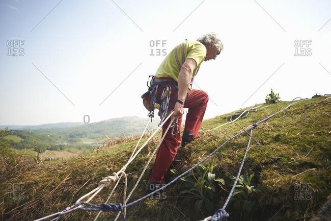 Rock climber on hillside preparing climbing rope