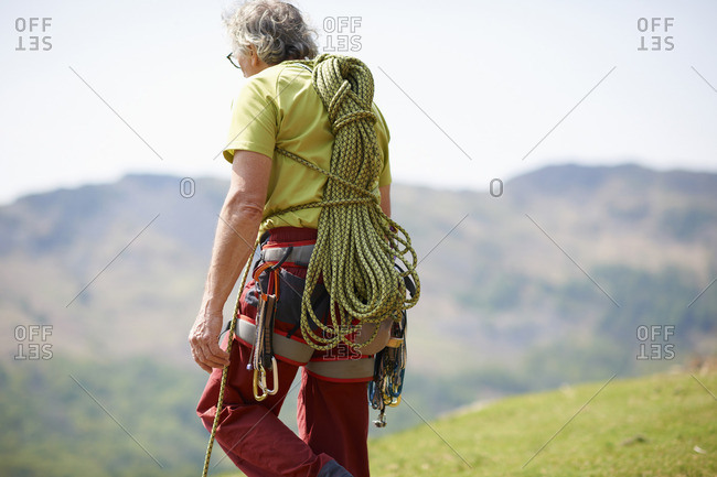 Rear view of rock climber carrying climbing rope on back