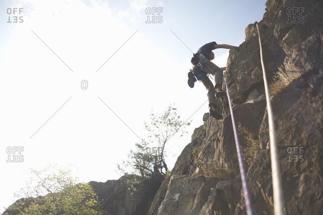 Low angle view of rock climber climbing rock face
